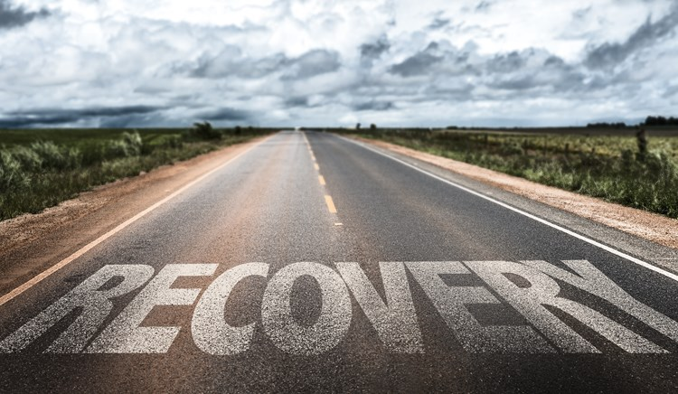 Close up on the word recovery and a long open road behind it