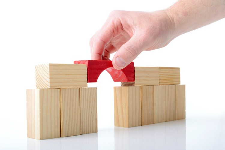 A hand placing a block to bridge the gap between other blocks