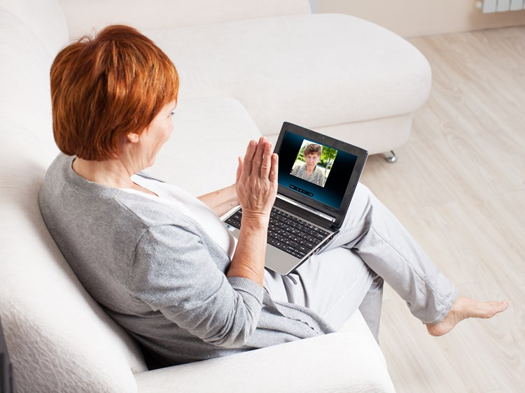 Caregiver communicating with loved one from vacation using video chat