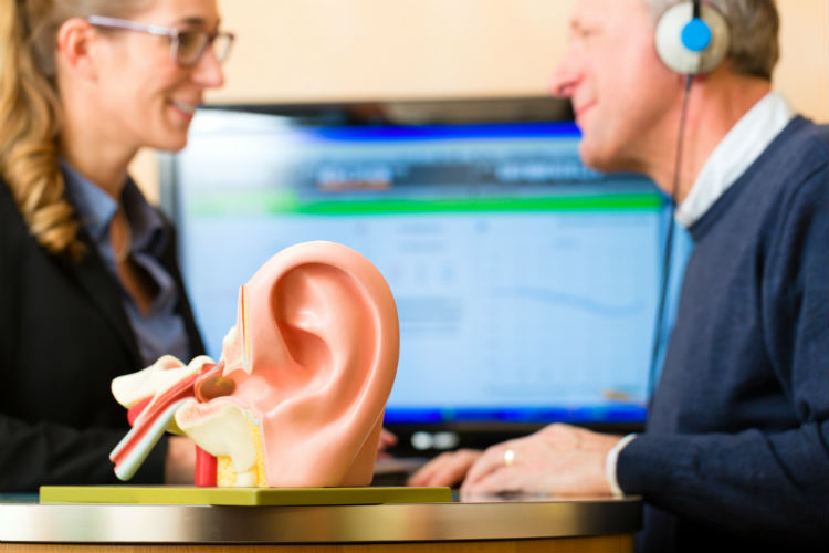 Man getting a hearing test from a woman with large ear in front