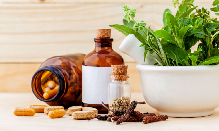 Various alternative therapies on a table, including supplements and fresh herbs