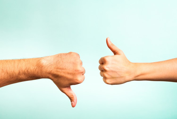 Two siblings hands facing each other one with thumbs down the other with thumbs up