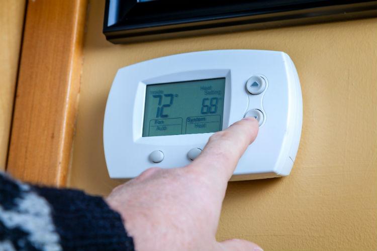 Senior adjusting the thermostat temperature