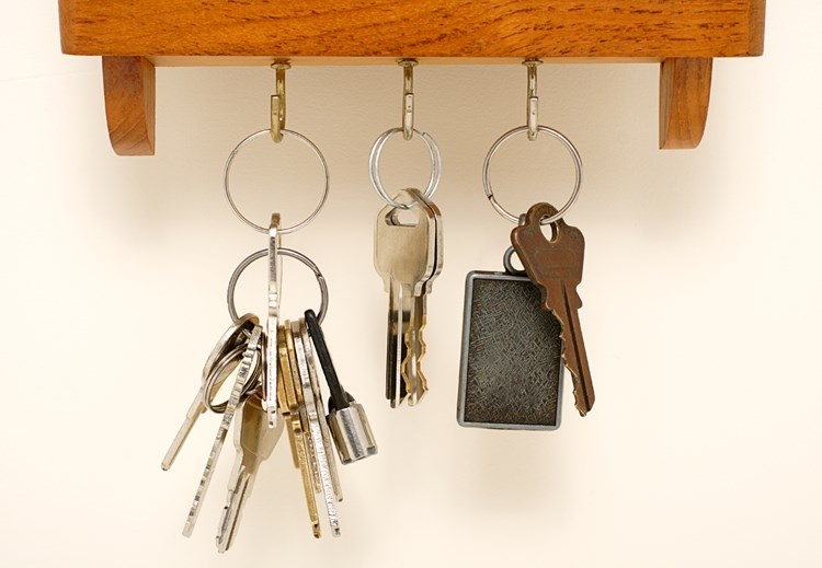 Three sets of keys hanging from hooks on a shelf
