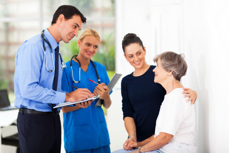 Elderly woman with her daughter talking to doctor and nurse