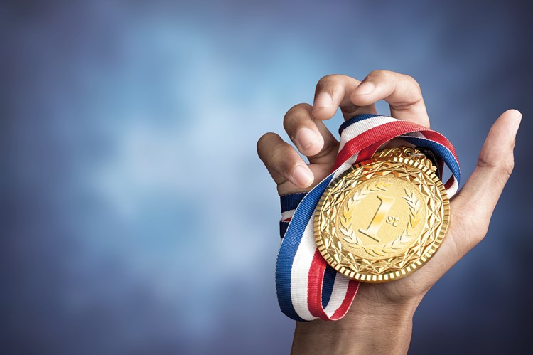 Hand holding first place caregiver olympics medal