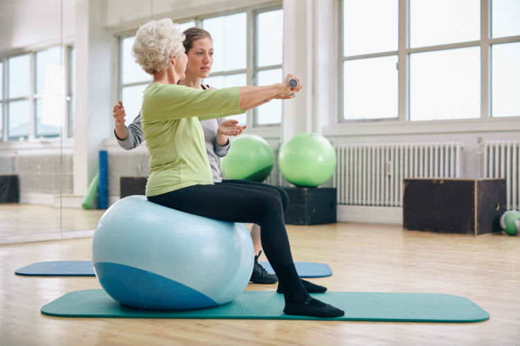 Female physical therapist assisting a senior woman on workout ball