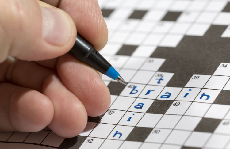 """Man doing crossword puzzle holding pen and the words """"train"""" and """"brain"""" already written in crossword"""