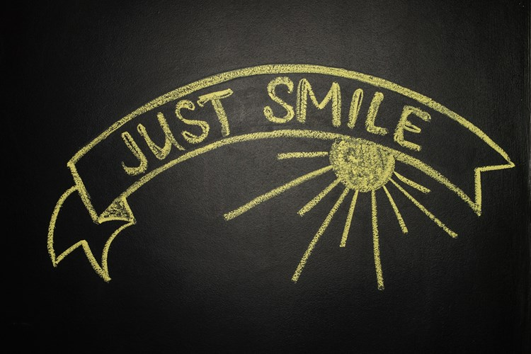 "Text on a chalkboard that reads ""just smile"" in yellow chalk"