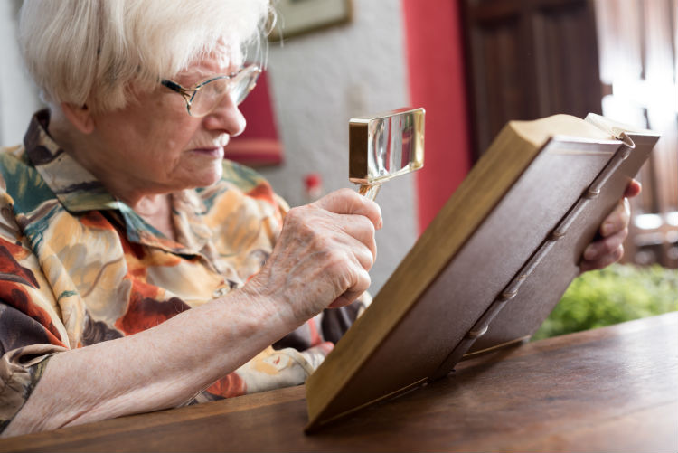 Woman reading book with magnifying glass