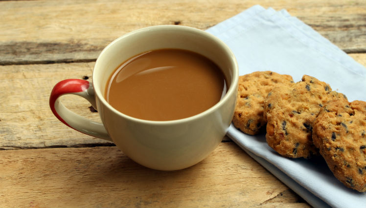 A mug off coffee and cookies on a table