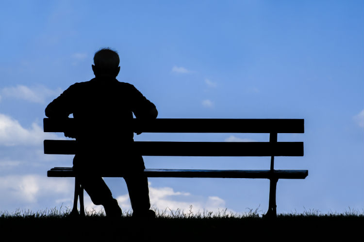 Man sitting alone on park bench at dusk