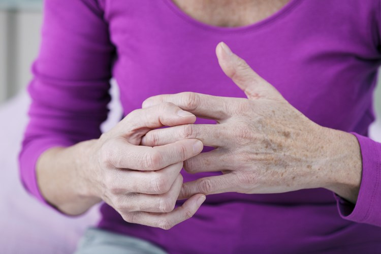 elderly woman holding knuckles due to arthritis pain