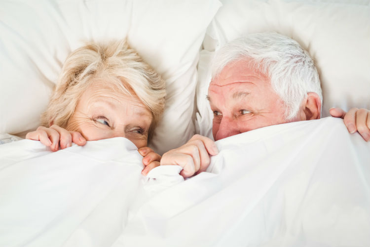 A senior couple in bed hiding behind the covers