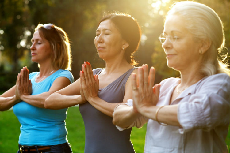 Three women with hands together doing yoga in park