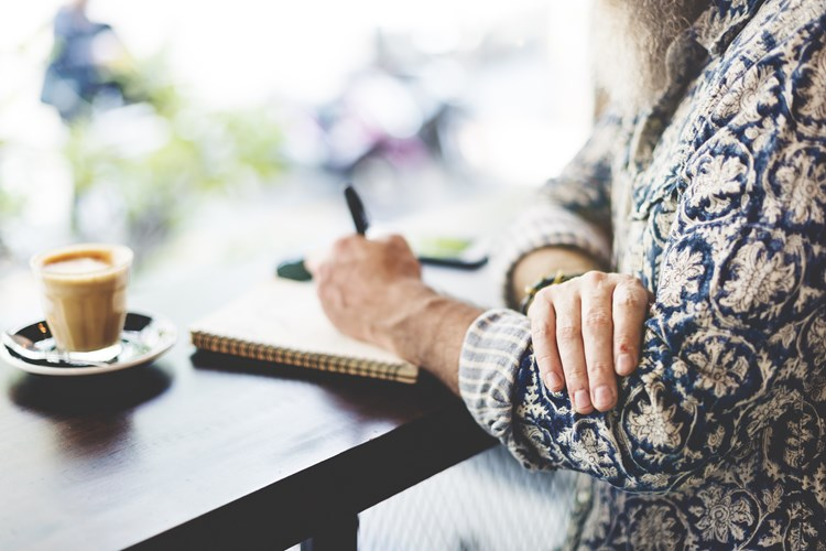 A caregiver sitting at a desk writing in their journal