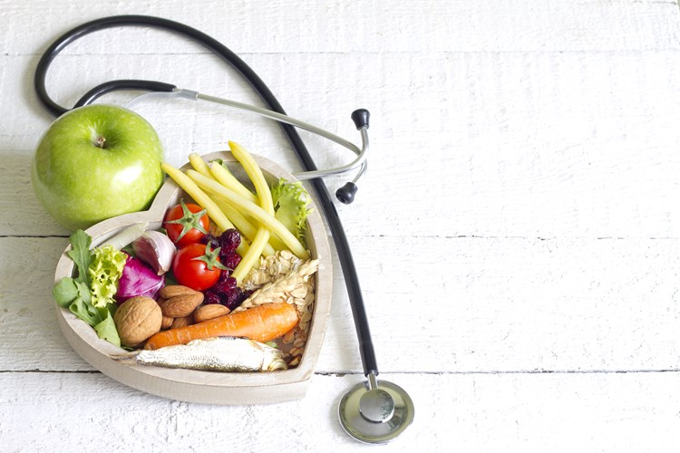 A heart shaped box filled with healthy food placed next to a stethoscope
