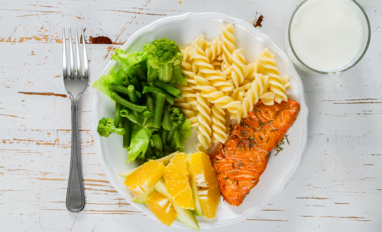 A nutritionally balanced meal of fruit, vegetables, fish, pasta, and milk