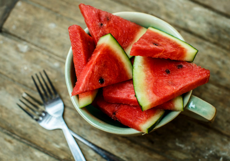 slices of watermelon in a bowl on a wooden table with forks on the side