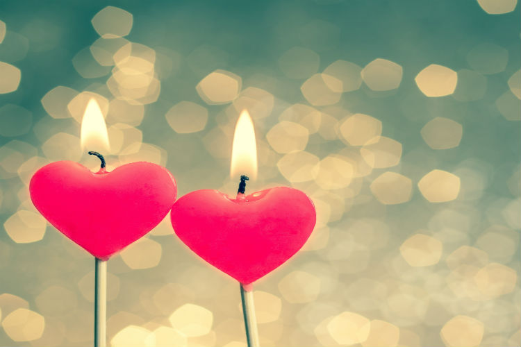 Two heart candles with their flames burning