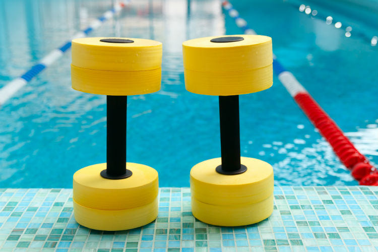 Two water weights standing up next to the edge of a pool