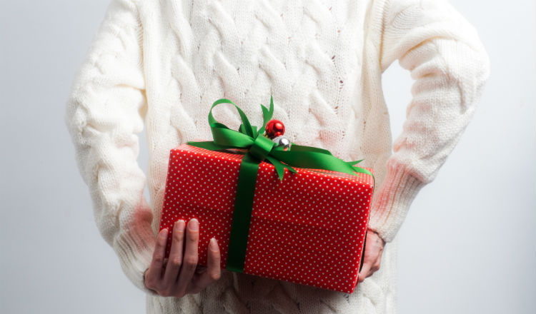Person in sweater holding a gift behind the back