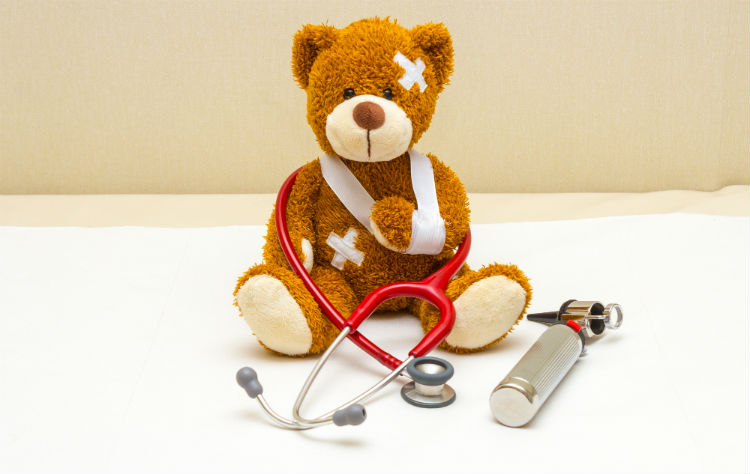 Teddy bear with bandages on doctor's examining table