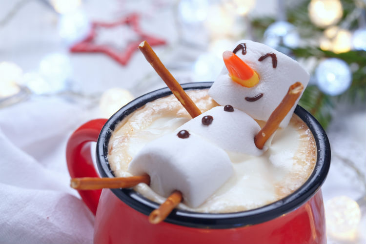 A happy marshmallow snowman laying in hot chocolate resembling a relaxed caregiver