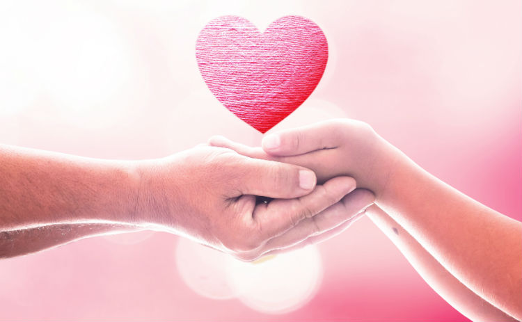A senior man holding his daughter's hands with a cartoon heart floating above the hands