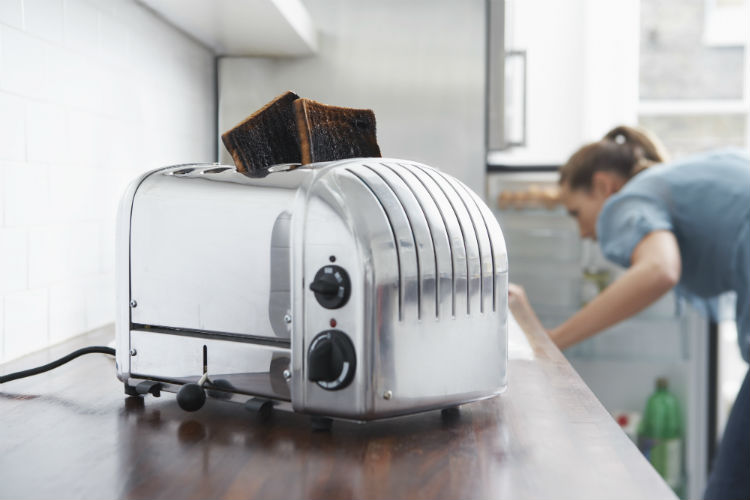 Burned toasts in toaster on kitchen counter with daughter looking in fridge.