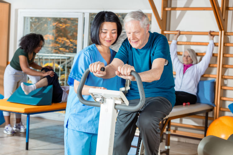 Nurse helping elderly man exercise for physical therapy