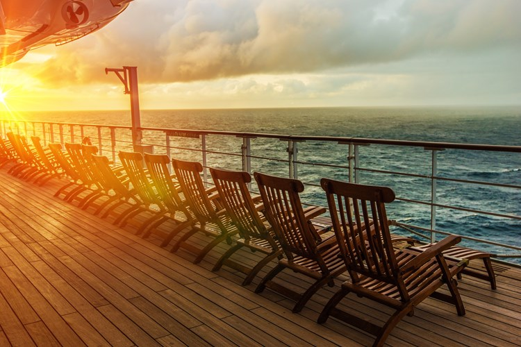 Sun chairs lined up on the deck of a cruise ship facing a sunset