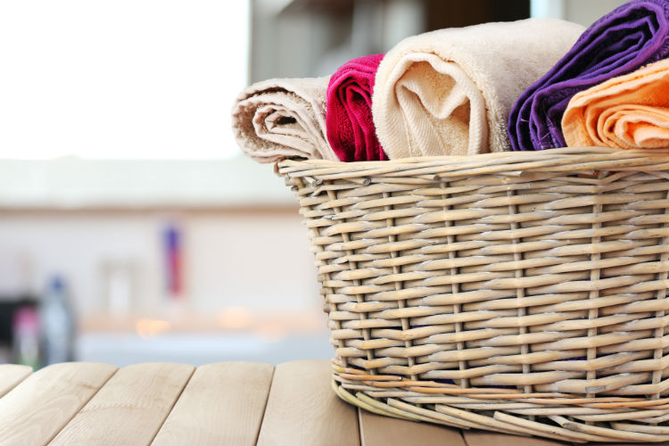 Basket of colorful towels on a bathroom bench with bathtub in background