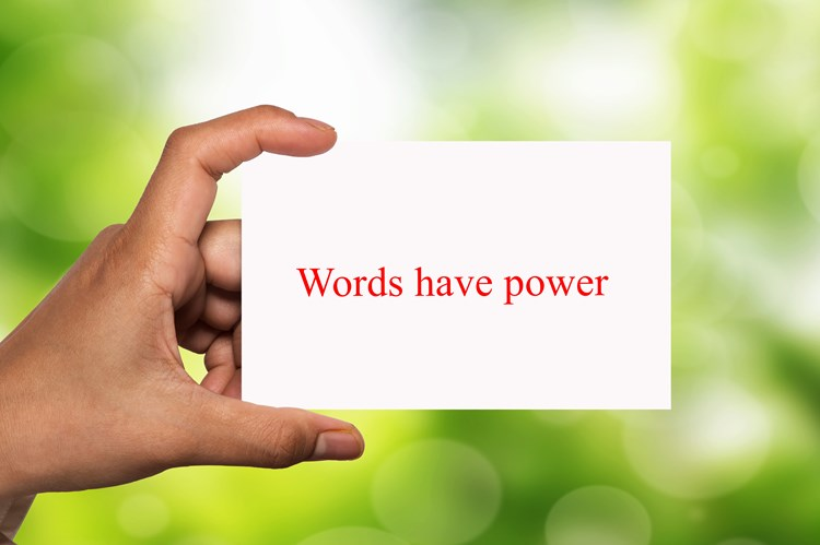 "A hand holding up a note card that reads ""words have power"" in red text"