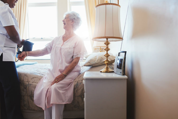 Woman in assisted living smiling in her bed talking to a caregiver
