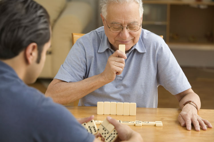 Senior man playing dominoes with adult day care staff