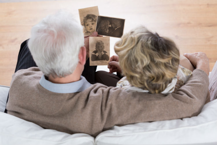 Senior couple sitting on sofa looking at old pictures