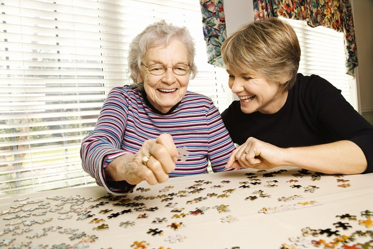 A family caregiver doing a puzzle activity with their loved one