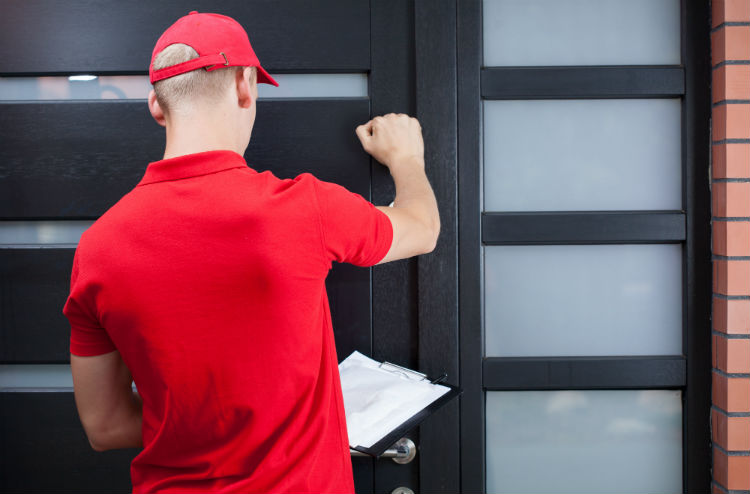 Man in red shirt knocking on door with clipboard