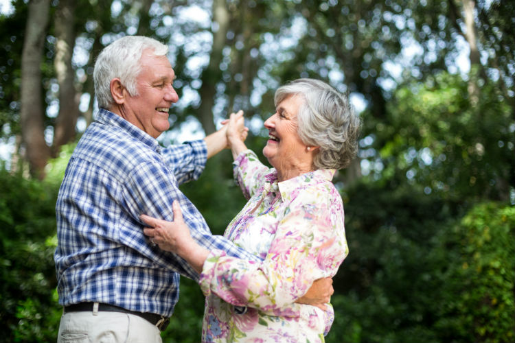 Two senior adults smiling and dancing