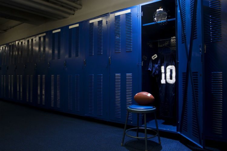 Football locker room with open locker with chair and football
