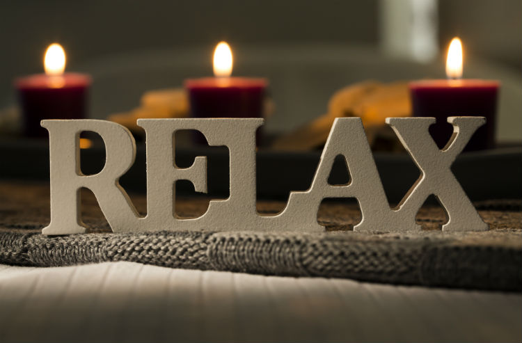 Wooden letters spelling relax with lit candles in background