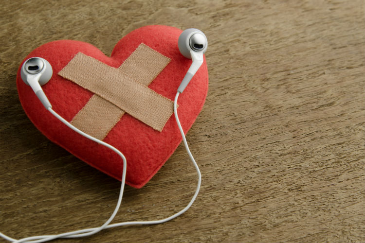 A heart with a bandage on it with headphones resting on top of it
