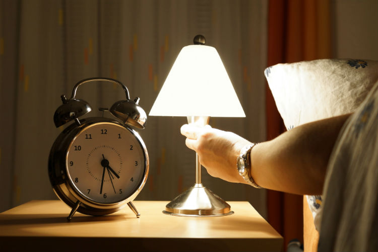 Woman turning off light on end table with alarm clock