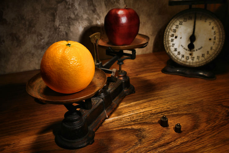An apple and an orange on a scale, weighing the differences