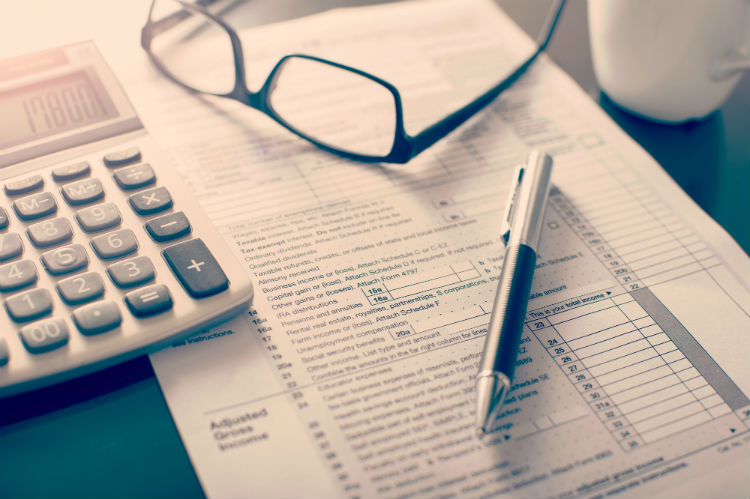 tax document with calculator, pen, and glasses