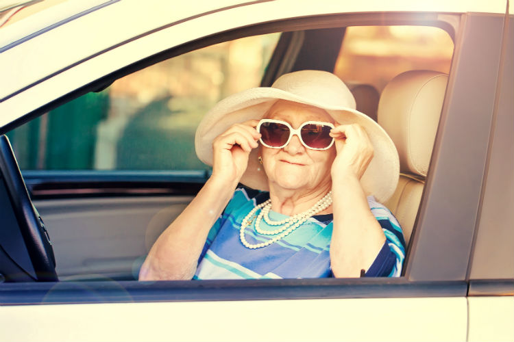 Older woman in the driver seat of a car adjusting her sunglasses