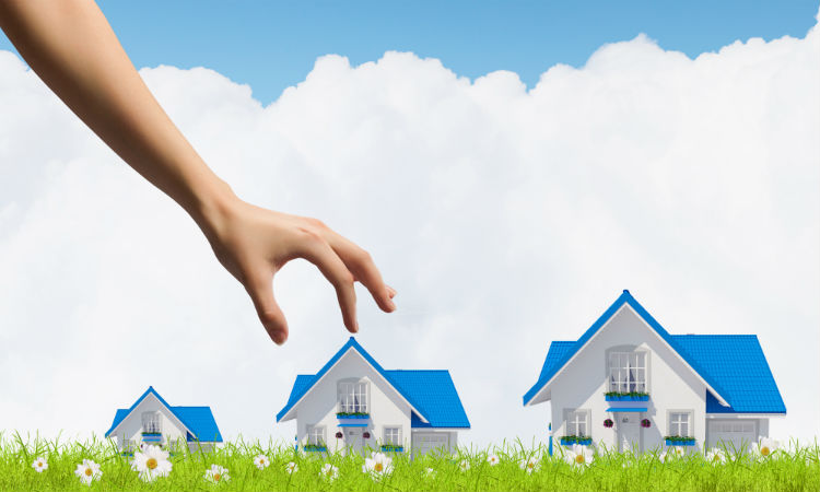 Hand selecting preferred home out of three homes