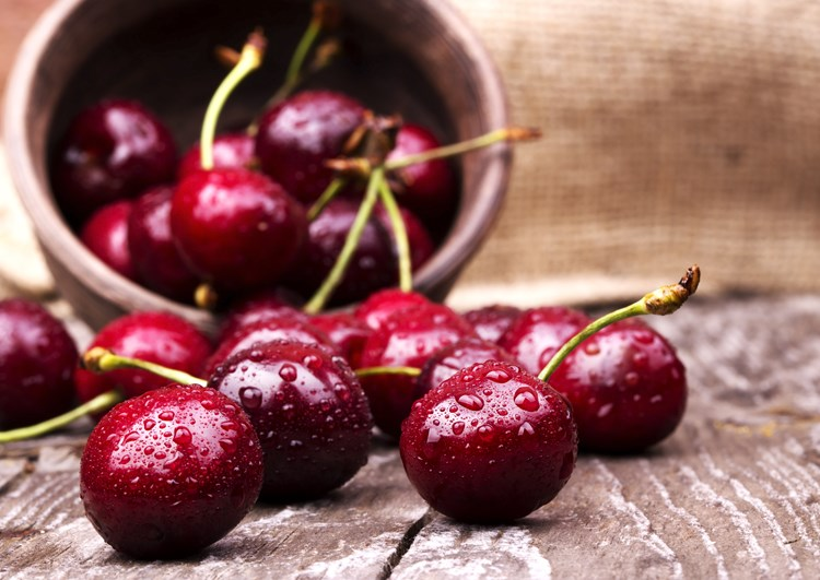 A close up on a bowl of cherries with a bowl tipped over in the background