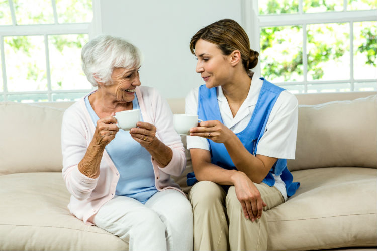 Older woman sitting on the couch having a conversation with her caregiver